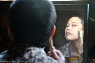 Burmese woman applying Thanaka on her face